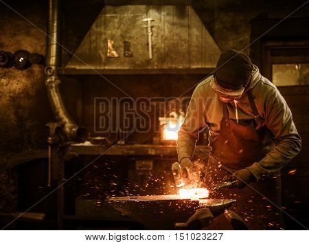 The blacksmith forging the molten metal on the anvil in smithy.