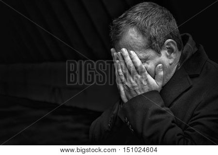 Misfortune. Portrait of unhappy middle-aged man. He covered his face with his hand.