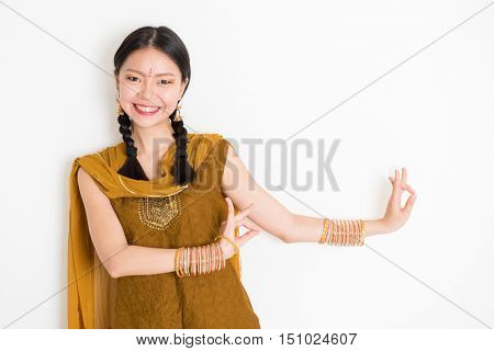 Portrait of young mixed race Indian Chinese girl dancer in traditional punjabi dress with dancing pose, standing on plain white background.