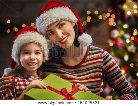 Merry Christmas! Mother and her daughter child girl exchanging Christmas gifts