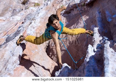 Top View of Smiling Male Extreme Climber in bright sportive Clothing hanging on unusual shaped Rock bright Daylight Outdoors orange and blue Colors of Stone
