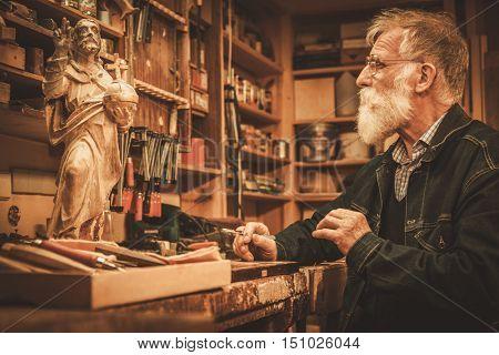 Senior restorer working with antique decor element in his workshop.