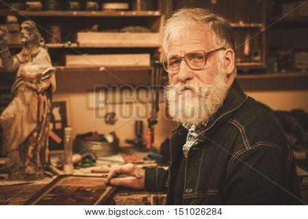 Portrait of senior restorer in his workshop.