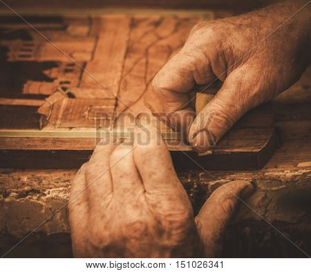 Close-up of restorer hands working with antique decor element in his workshop.