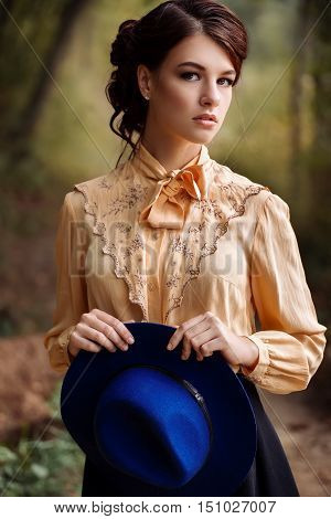 Outdoor closeup fashion portrait of sensual young stylish lady with trendy hat. Autumn portrait of woman. Fashion woman with romantic hairstyle and floppy hat. Closeup portrait of young beautiful brunette girl with brown eyes. Looking at camera