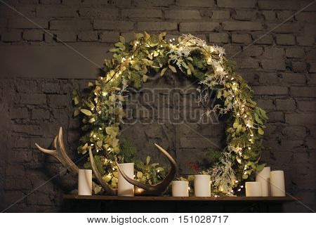 Christmas wreath above mantel on brick wall background with lights candles and deer antler