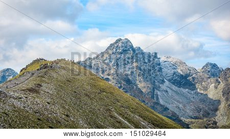 group of hikers admires view from Kasprowy Wierch on Swinnica mountain in Hight Tatras, Poland