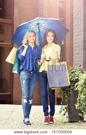 Attractive girls walking in a city center. Women with a shopping bags. Friends spending money. Discount, sales and shopping concept.