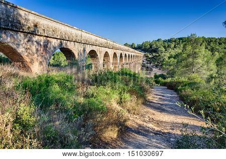 Lateral view on archade of roman aqueduct near Tarragona, summer Spain