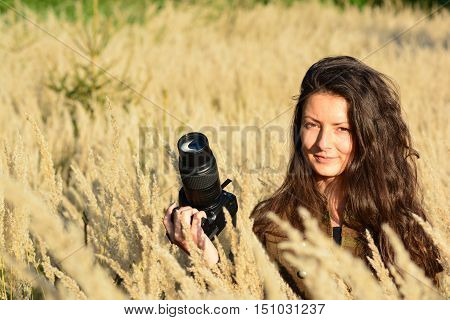 Portrait of young long haired brunette girl nature photographer in tall golden colored grass in the middle of autumn field in afternoon sunlight