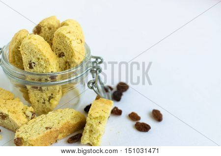Homemade raisins cookies on white baclground with place for text. Jar with freshly baked raisin cookie. Healthy breakfast. Tasty cookies for an afternoon snack. Selective Focus. Copy space.