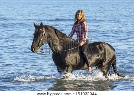 horse woman and her stallion riding in the sea