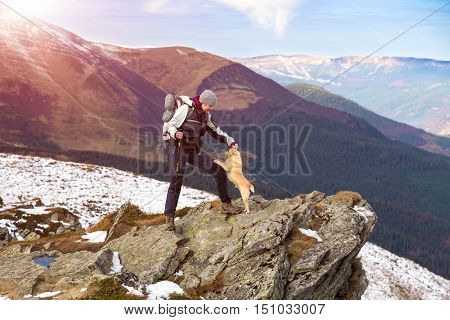 Female Hiker with Backpack and walking Poles staying at rocky Mountains Cliff and playing with accompanying Dog view with green Hills and Sky on Background