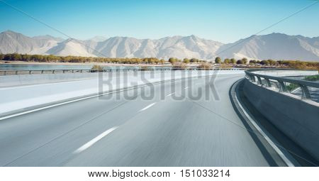 Highway overpass motion blur with mountain background .