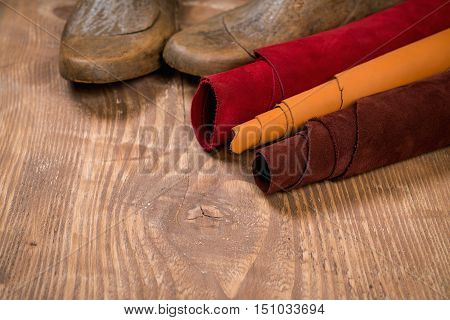 Leather in rolls and shoe lasts on wooden background. Leather craft. Copy space. Workplace for shoemaker