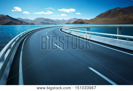 Highway overpass motion blur with mountain lake background .