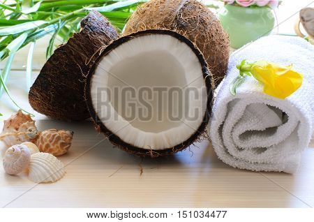 Coconut towel towel with tropical flowershells and candles on light wood background for spa concept.