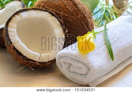 Coconut towel towel with tropical flower and candles on light wood background for spa concept.