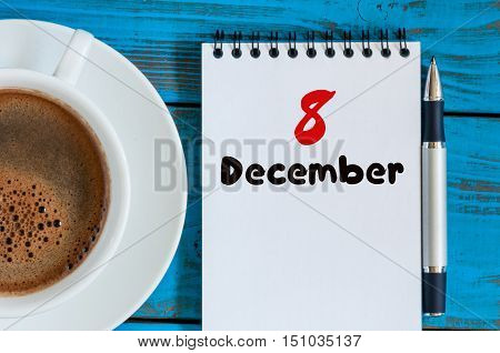 December 8th. Day 8 of month, calendar on freelancer workplace background with coffee cup. Top view. Winter time. Empty space for text.