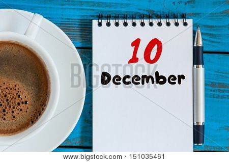 December 10th. Day 10 of month, calendar on freelancer workplace background with coffee cup. Top view. Winter time. Empty space for text.