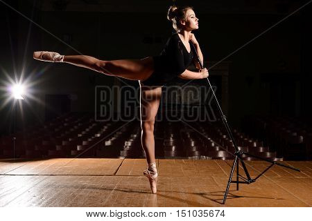 Pretty ballerina in pointe shoes making flap leg holding hands on the rack on the stage