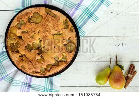 Home baked biscuit flavored pear charlotte cake with cinnamon. On a white wooden background. The top view.