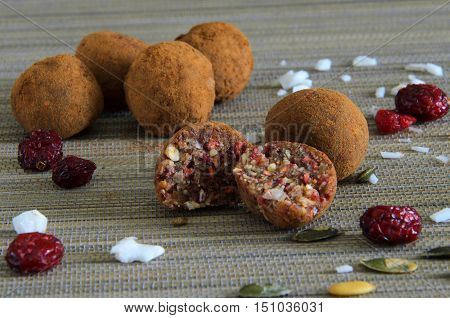 Raw chocolate candies with nuts figs seeds coconut and cranberries. Vegan truffles for healthy dessert.