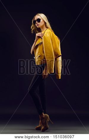 Beautiful, tall, slim fashion model in yellow jacket posing on black background full lenght.