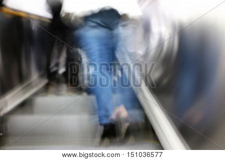 Woman's legs from behind on subway escalator.