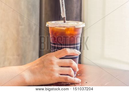 Woman's hand holding iced coffee in takeaway cup.