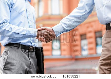 African American businessman and a Caucasian businessman shaking hands on the background buildings, close-up