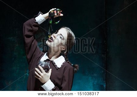 Portrait of a young girl with snakes. Girl in school uniform as killer. The image in the style of Halloween