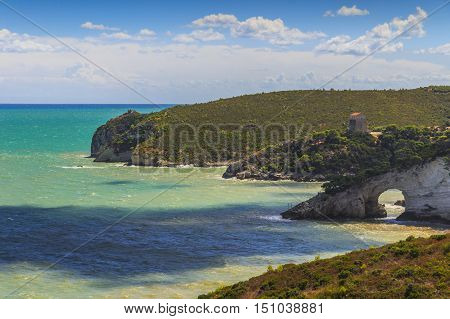 Gargano coast:San Felice Bay (Architello),Italy.Gargano National Park,The little rock arch (San Felice Arch or Architello) is spectacular symbol of Vieste.In the background the watchtower San Felice.
