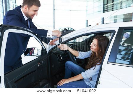 poster of Car salesman sells a car to happy customer in car dealership and hands over the keys