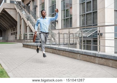 Young African American businessman with briefcase running down the street of the city. late for work
