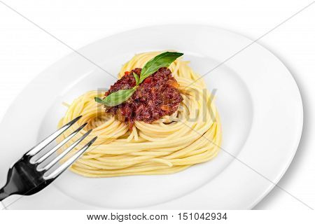 Cooked spaghetti carefully arranged in a heart shape and topped with tomato sauce accompanied by raw ingredients to the side