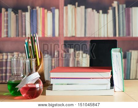 Still life with books, colored pencils, tablet and chemical glassware on bookshelf backgroud