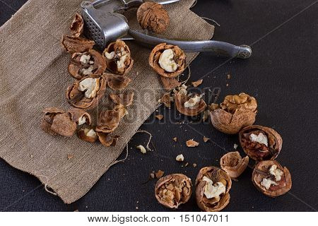 walnuts and a nutcracker on a table covered with burlap