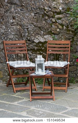 Foldable wooden chairs, mini table with candle lantern on top placing outdoor by stone wall