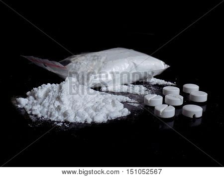 Cocaine drug powder bag, pile and lines, pills on black background