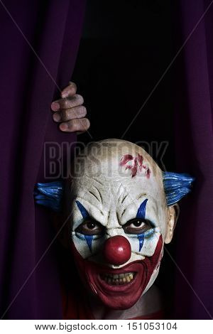 closeup of a scary evil clown peering out from a purple stage curtain