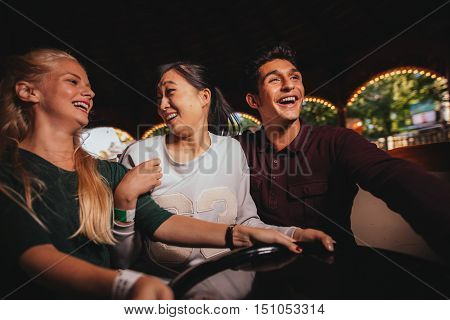 Young man and women on amusement park ride. Group of friends having fun together.