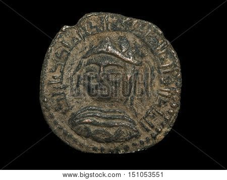 Ancient Bronze Islamic Coin With Portrait Of A Ruler Isolated On Black