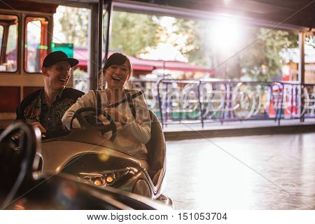 Happy young man and woman driving bumper car at fairground. Young couple riding bumper car at amusement park.