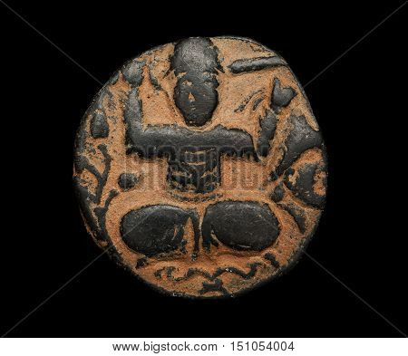 Ancient Bronze Coin With Image Of Person Seated In Lotus Position Isolated On Black