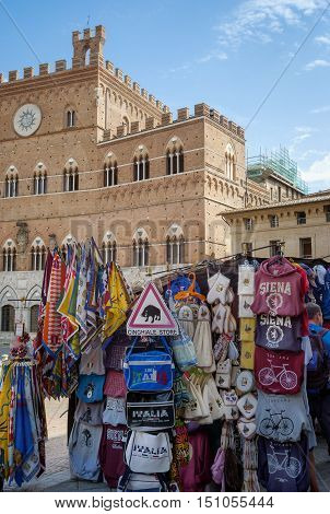 SIENA, ITALY - AUGUST 30, 2016: some characteristic souvenirs stall for the thousand tourists in the Piazza del Campo, world famous for the historical Palio; in the background the reinassance facade of the Palazzo Pubblico.