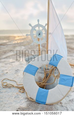 on the shore of the sea dekoratsiya- boat steering wheel and lifebuoy