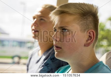 Young teenage boy watching something intently staring to the left side of the frame close up head shot