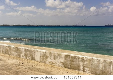 Waterfront stone promenade overlooking the ocean on a calm sunny blue sky day with clouds with distant ships and a shoreline