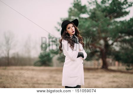 Beautiful Fashionable Woman In A Black Hat And White Coat Posing Outdoors